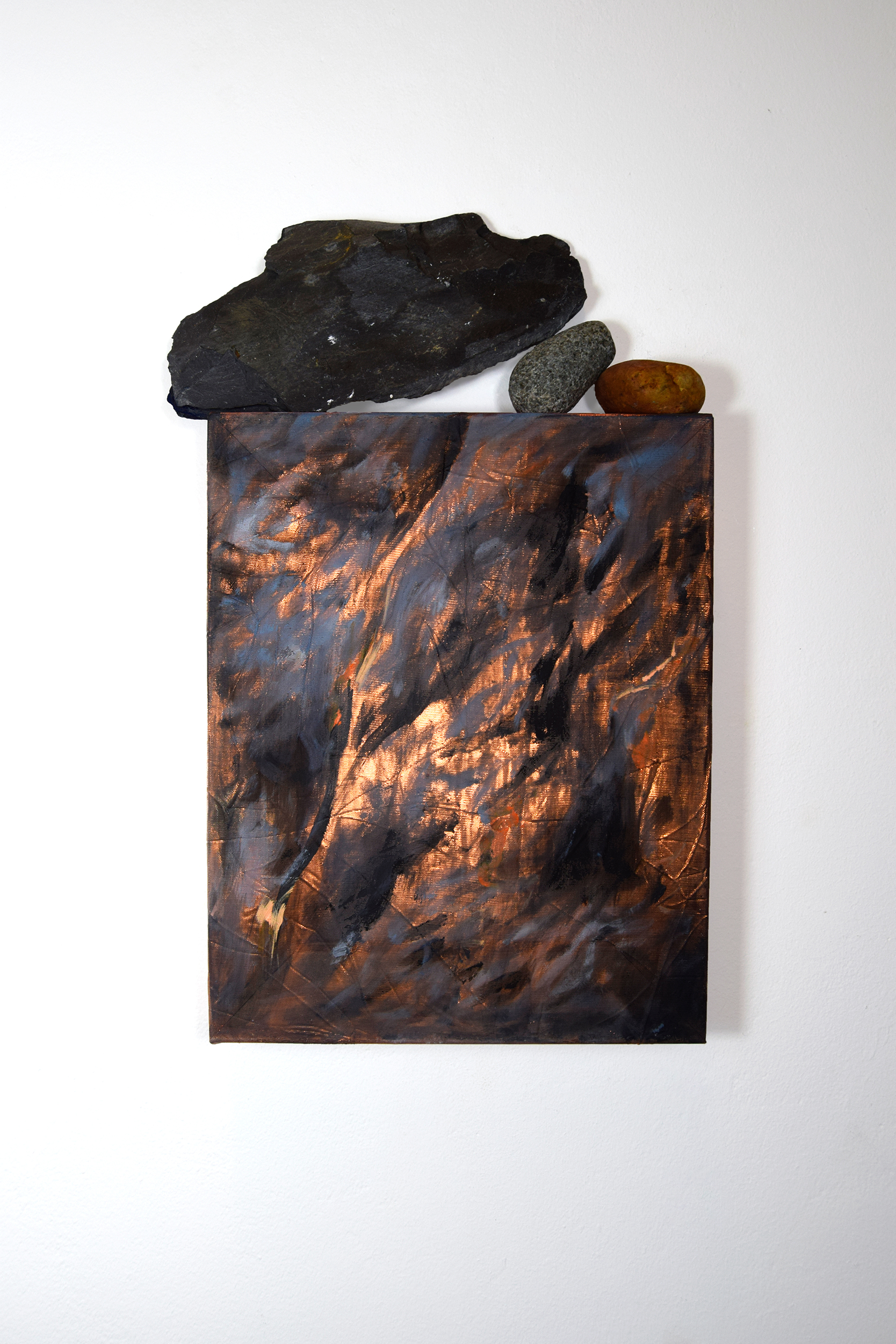 Cliff face painting on shiny orange fabric with stones balanced on top