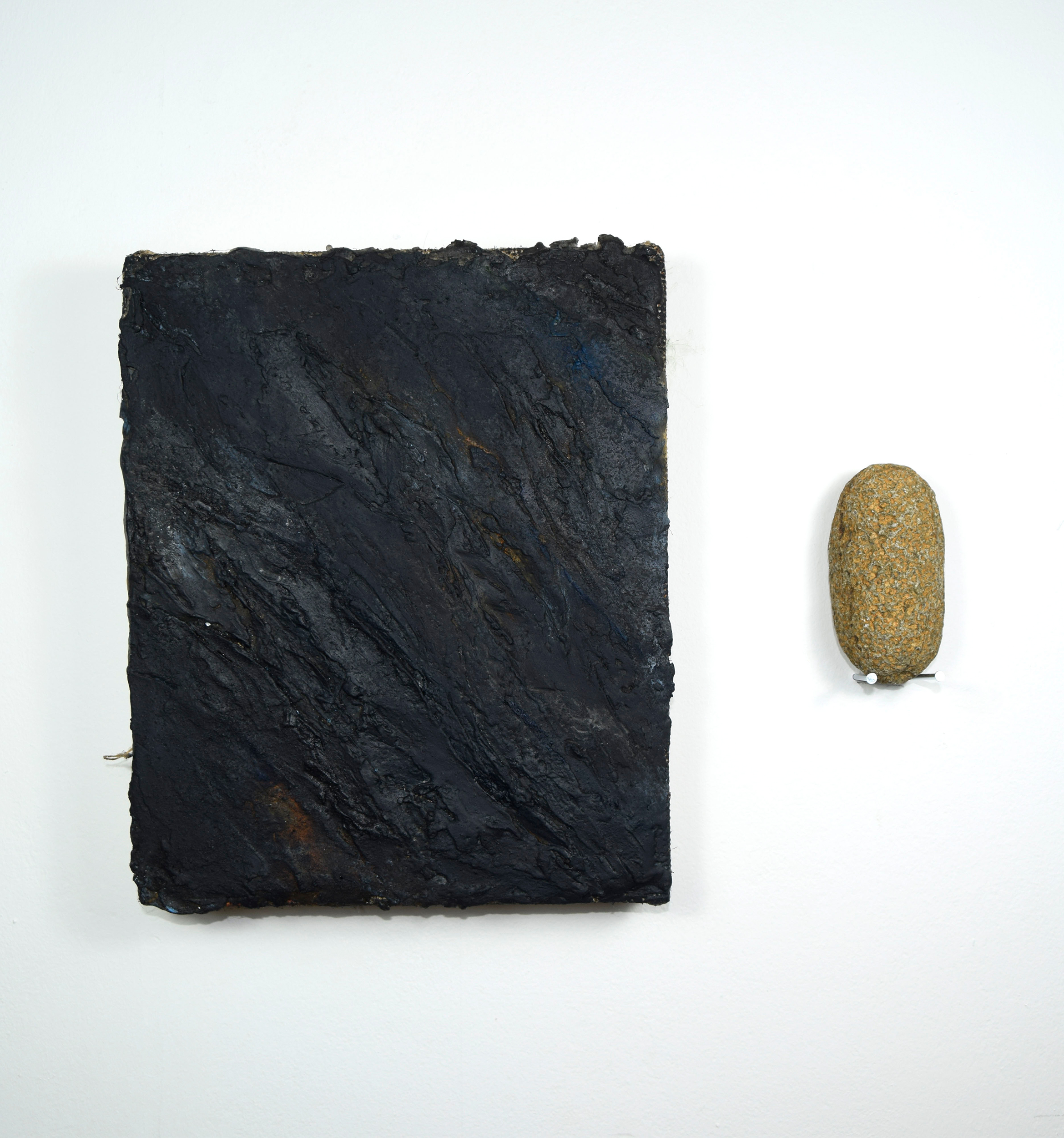 Almost black textural painting depicting slate with a pill shaped orange rock