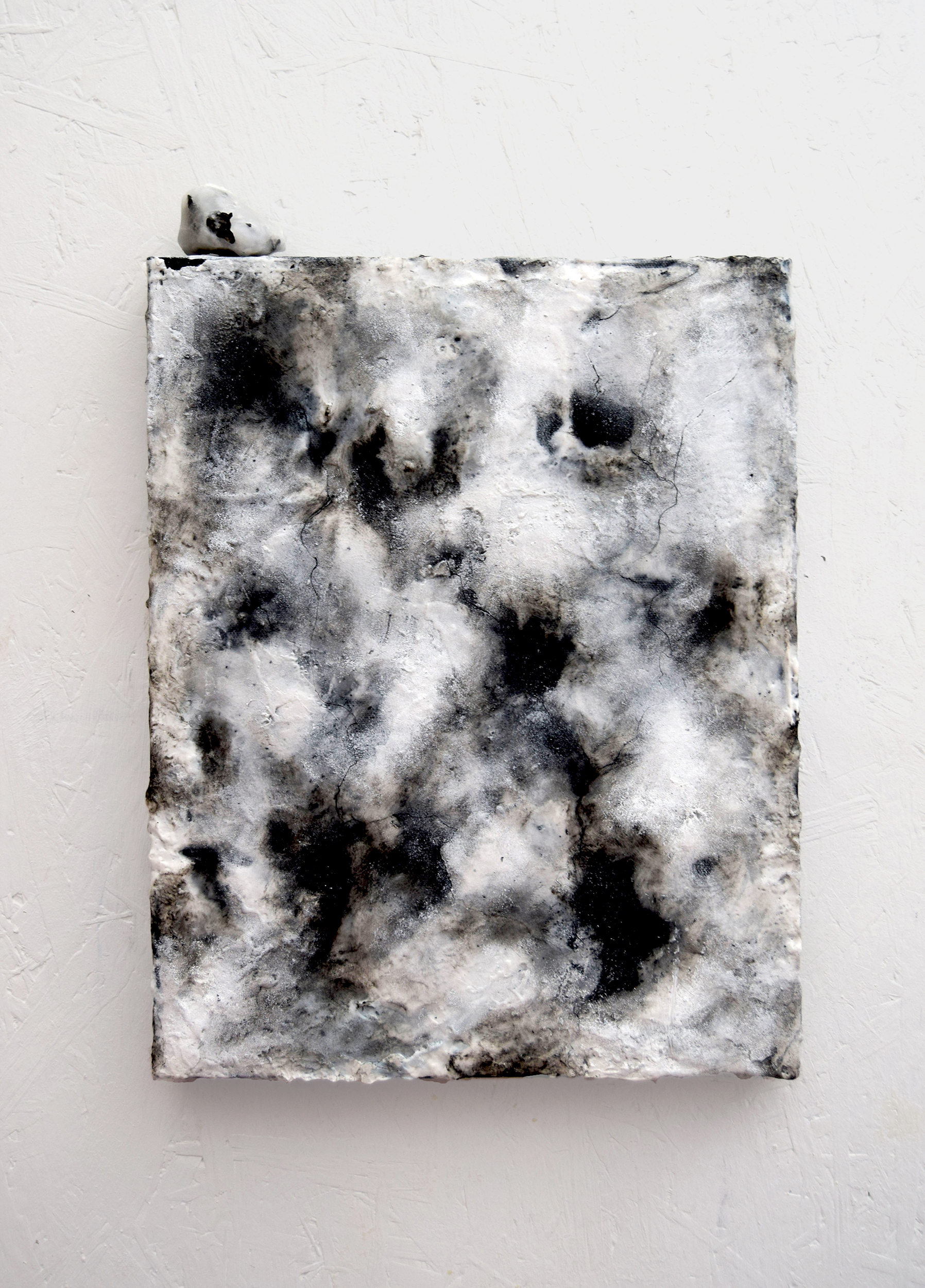 Black and white textural painting which looks like ice melting with a small sculpture placed on top